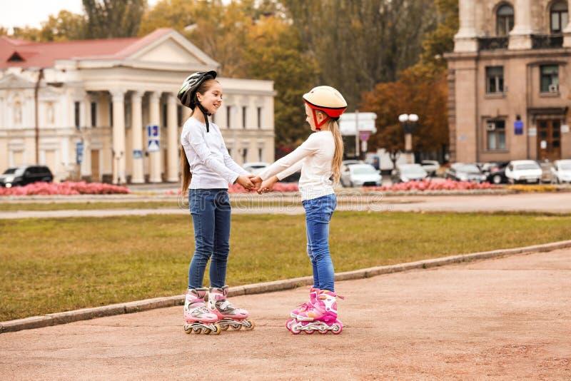 Crianças felizes que vestem patins de rolo fotografia de stock