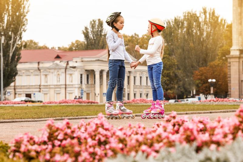 Crianças felizes que vestem patins de rolo foto de stock