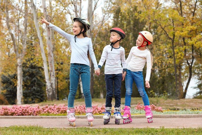 Crianças felizes que vestem patins de rolo imagens de stock royalty free