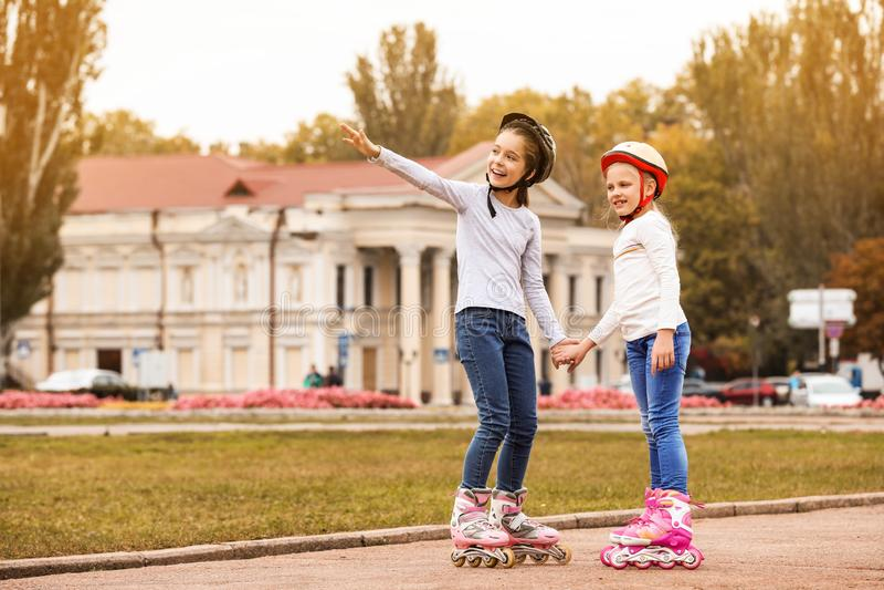 Crianças felizes que vestem patins de rolo foto de stock royalty free
