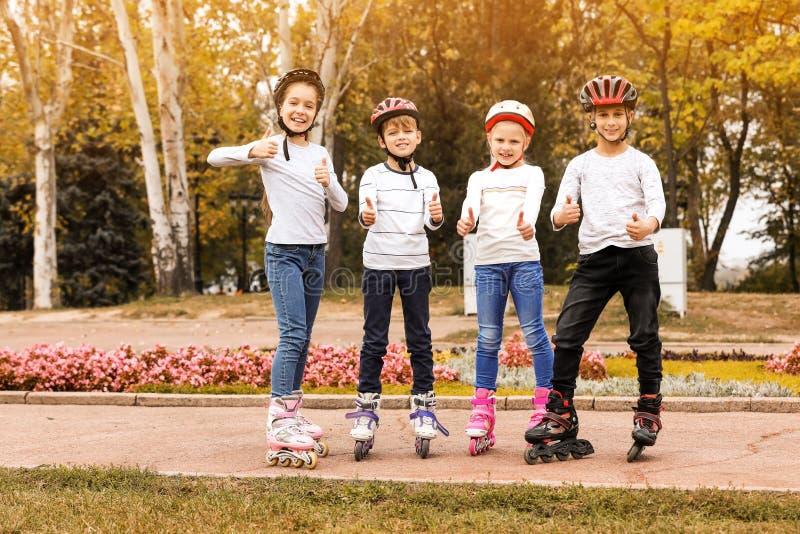 Crianças felizes que vestem patins de rolo no parque foto de stock