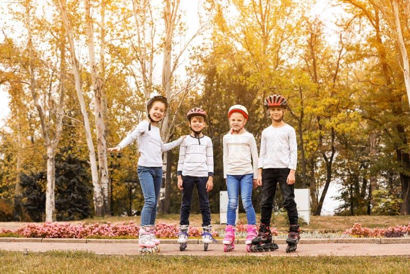 Crianças felizes que vestem patins de rolo no parque imagem de stock royalty free
