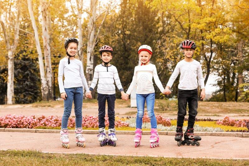 Crianças felizes que vestem patins de rolo no parque imagens de stock royalty free