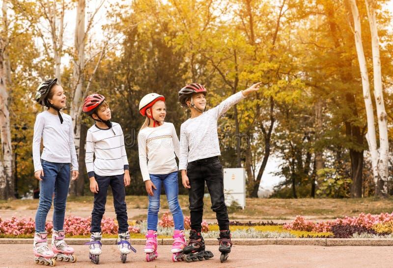 Crianças felizes que vestem patins de rolo no parque do outono imagem de stock royalty free