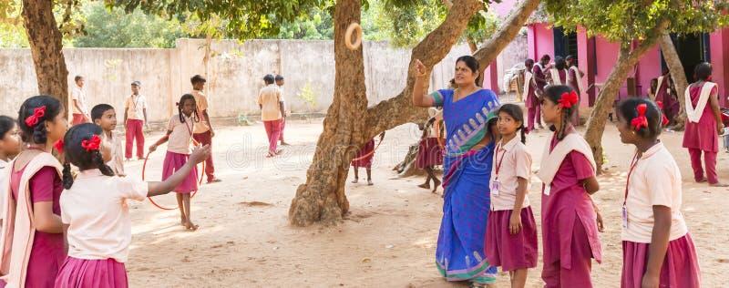 Crianças indianas autênticas com os uniformes no campo de jogos na escola primária imagens de stock
