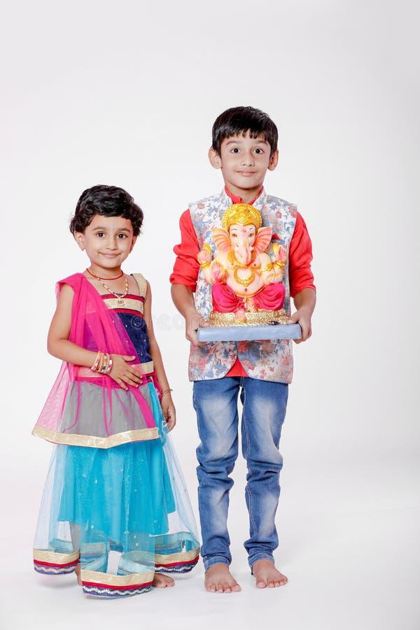 Crianças indianas pequenas com ganesha e rezar do senhor, festival indiano do ganesh foto de stock royalty free