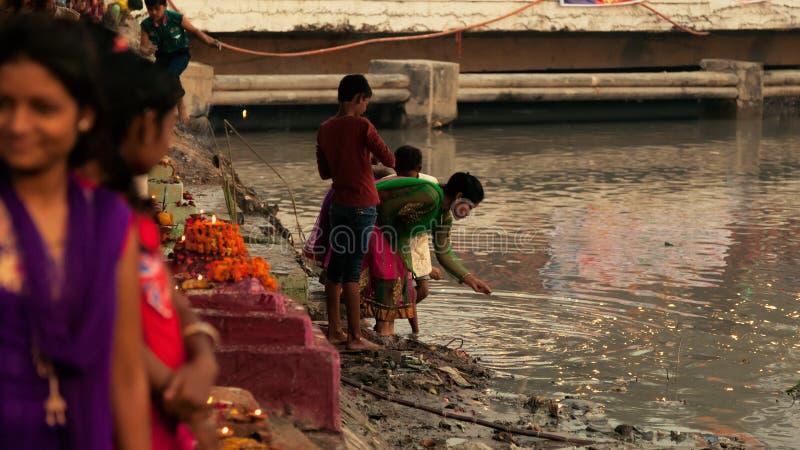 Crianças indianas que permorming o pooja de Chhath no rio imagem de stock