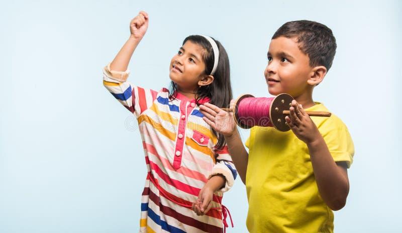 2 crianças indianas que voam o papagaio, uma que guarda spindal ou chakri fotografia de stock royalty free
