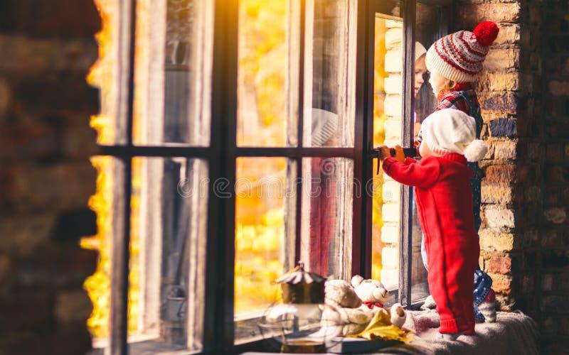 Crianças irmão e irmã que admiram a janela para o outono imagens de stock
