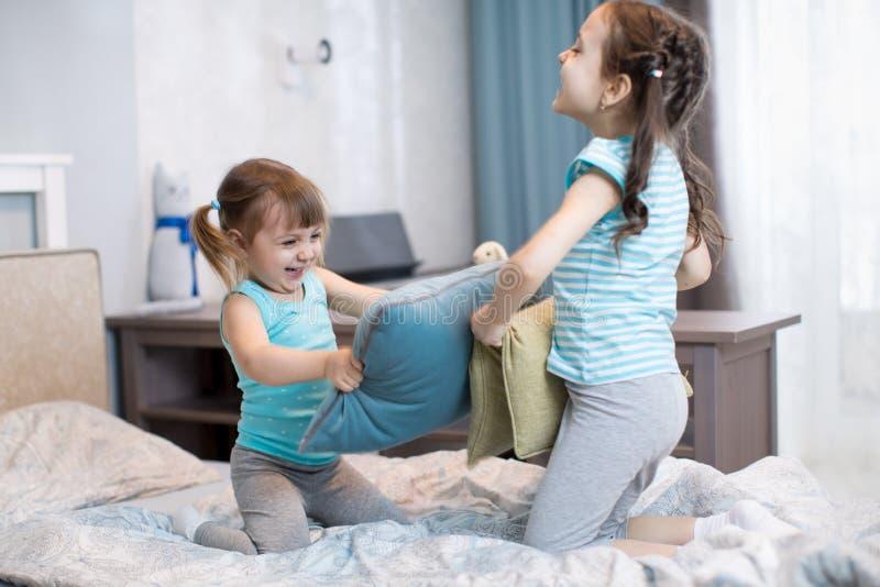 Crianças irmãs se divertem brincando com travesseiros em casa fotografia de stock