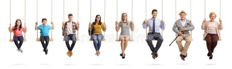 Crianças, jovens e sêniores sentando balanços e sorriso do OM imagens de stock