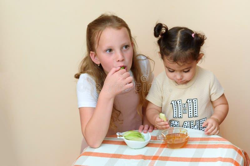 Crianças judaicas que mergulham fatias da maçã no mel em Rosh HaShanah imagens de stock royalty free
