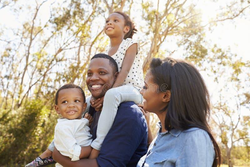 Crianças levando da família em ombros como andam no parque foto de stock royalty free