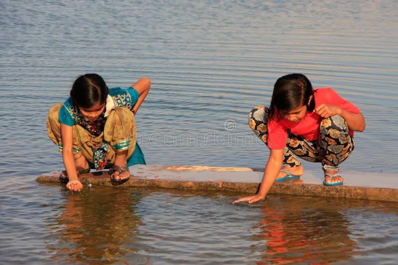 Crianças locais que bebem das reservas de água, vila de Khichan, Índia foto de stock royalty free
