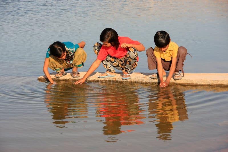 Crianças locais que bebem das reservas de água, vila de Khichan, Índia fotografia de stock royalty free