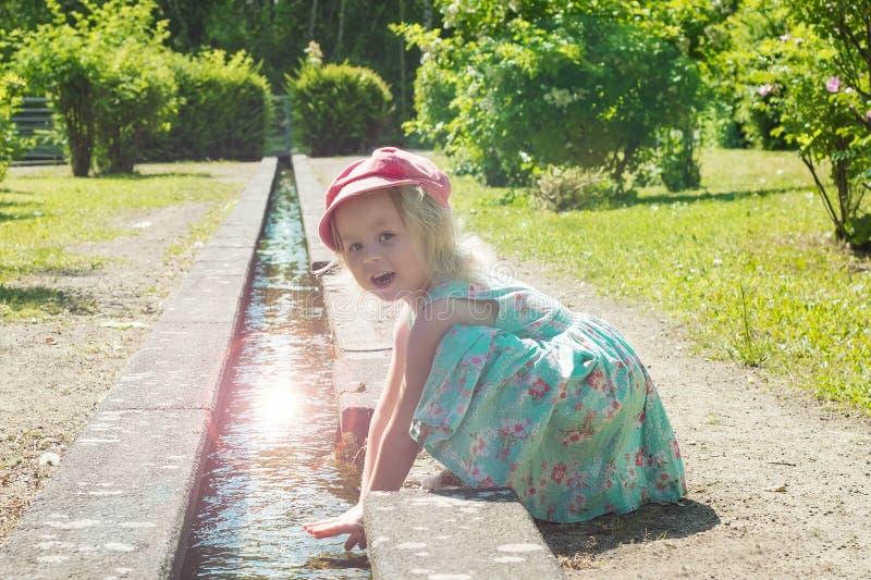 Crianças, menina que joga com água em uma fonte que tem uma nadada Em um dia ensolarado do verão foto de stock