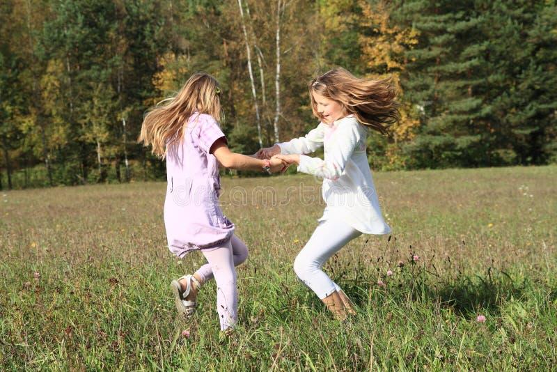 Crianças - meninas que dançam no prado fotografia de stock