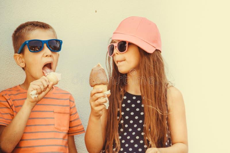 Crianças menino e menina que comem o gelado foto de stock royalty free