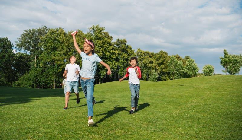 Crianças multi-étnicos felizes que jogam junto e que correm no prado verde no parque fotos de stock royalty free