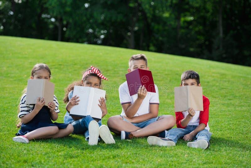Crianças multi-étnicos que guardam livros ao sentar-se no prado verde no parque imagem de stock royalty free