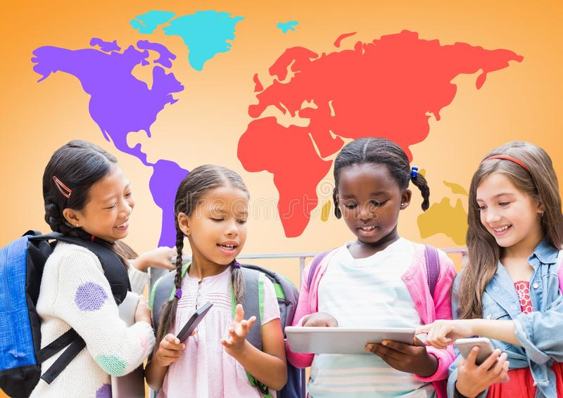 Crianças multiculturais em dispositivos na frente do mapa do mundo colorido fotografia de stock royalty free