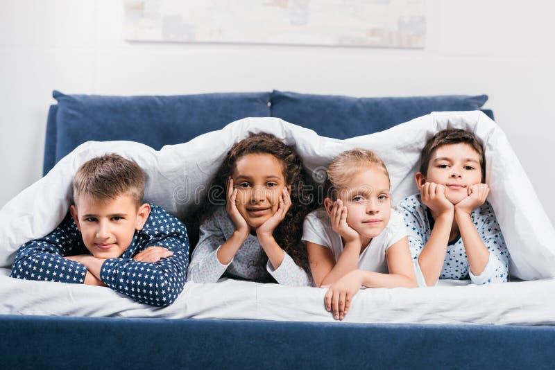 crianças multiculturais que olham a câmera ao encontrar-se junto na cama fotos de stock royalty free