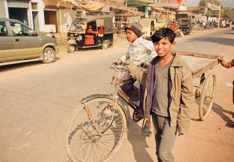 Crianças não identificadas que conduzem no carro da bicicleta através da rua indiana da sujeira na Índia fotografia de stock