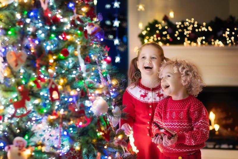 Crianças na árvore de Natal Crianças na chaminé na véspera do Xmas fotografia de stock royalty free