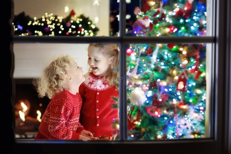 Crianças na árvore de Natal Crianças na chaminé na véspera do Xmas foto de stock royalty free