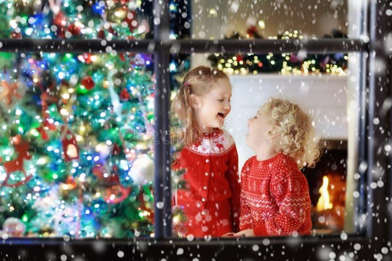 Crianças na árvore de Natal Crianças na chaminé na véspera do Xmas imagens de stock
