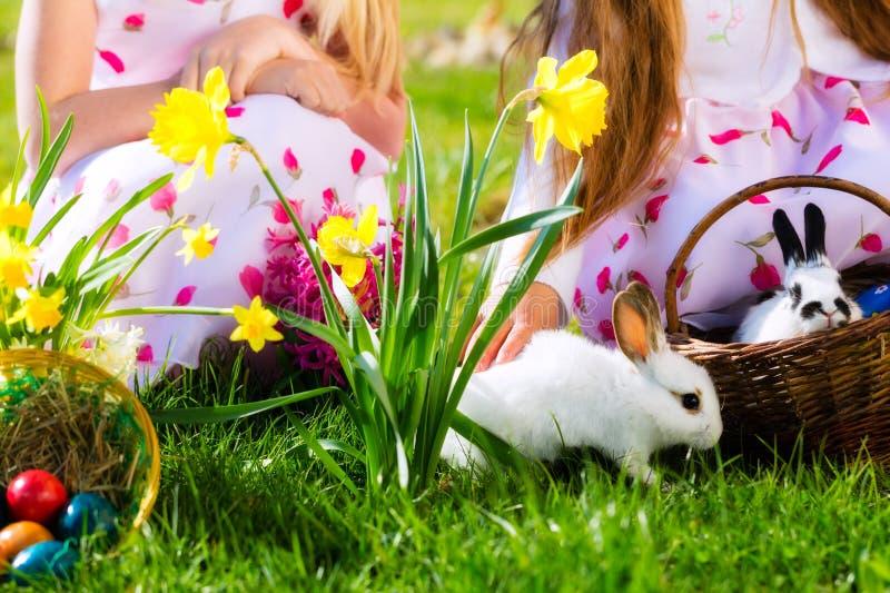 Crianças na caça do ovo da páscoa com coelho foto de stock royalty free