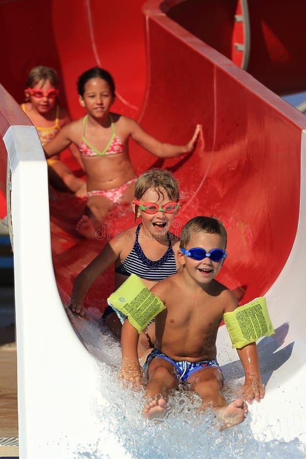 Crianças na corrediça de água no aquapark foto de stock royalty free