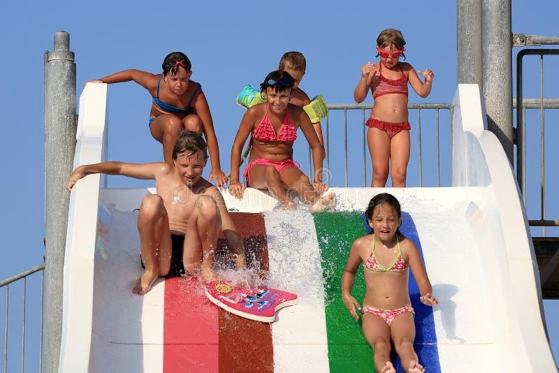 Crianças na corrediça de água no aquapark imagem de stock royalty free