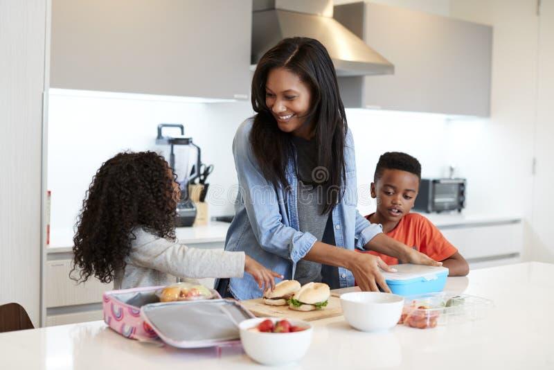 Crianças na cozinha em casa que ajuda a mãe a fazer o almoço embalado saudável fotos de stock royalty free
