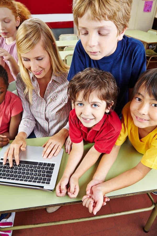Crianças na escola primária com portátil foto de stock