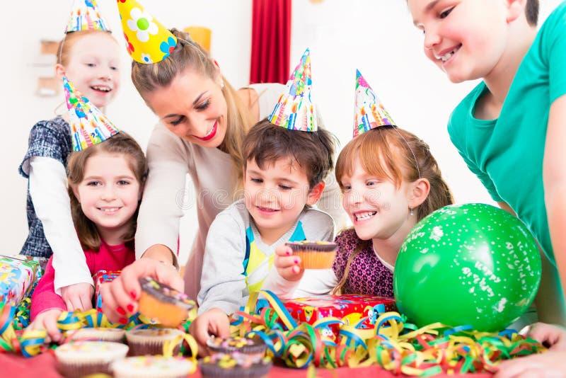 Crianças na festa de anos com queques e bolo imagens de stock