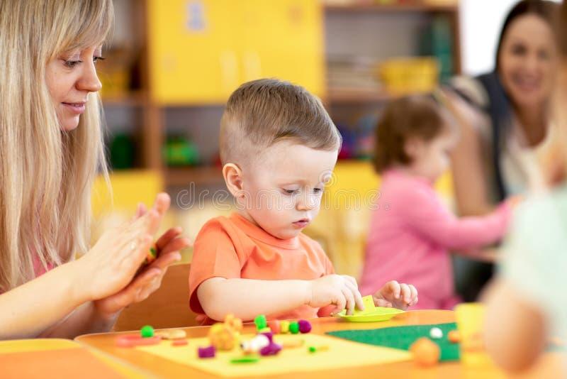 Crianças na lição no jardim de infância Criança do bebê que joga com plasticine com o professor na sala de jogos do berçário imagem de stock