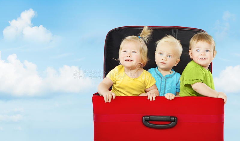 Crianças na mala de viagem, jogo feliz de três crianças fotografia de stock royalty free