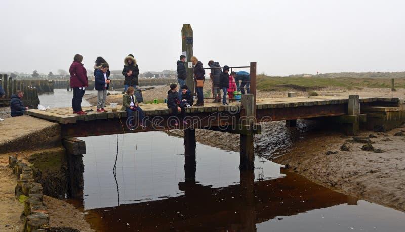 Crianças na ponte com linhas do caranguejo na água imagens de stock