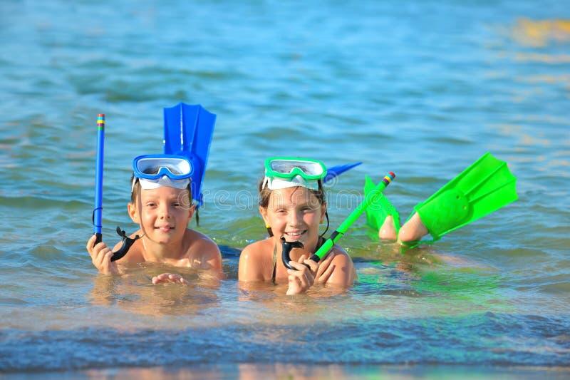 Crianças na praia com snorkles fotos de stock