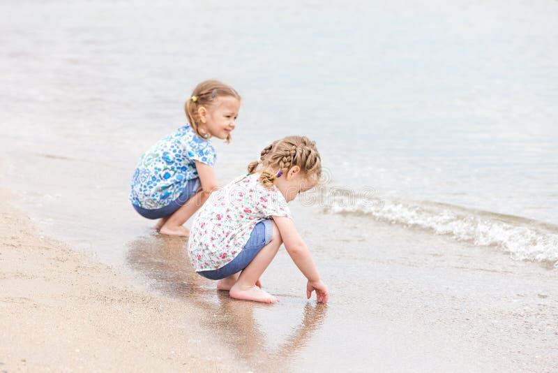 Crianças na praia do mar Gêmeos que sentam-se ao longo da água do mar fotos de stock