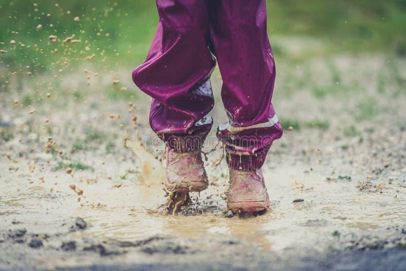 Crianças nas botas de borracha e na roupa da chuva que saltam na poça foto de stock
