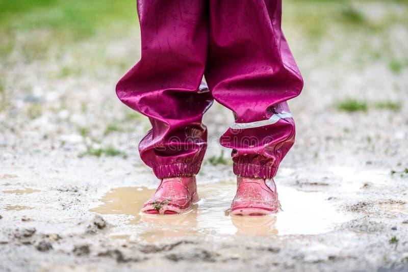 Crianças nas botas de borracha e na roupa da chuva que saltam na poça imagem de stock royalty free
