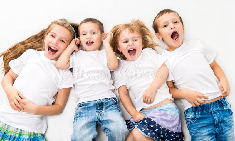 Crianças nas camisas brancas que encontram-se no assoalho foto de stock