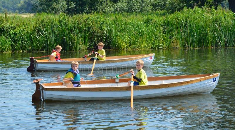 Crianças no barco de enfileiramento imagem de stock