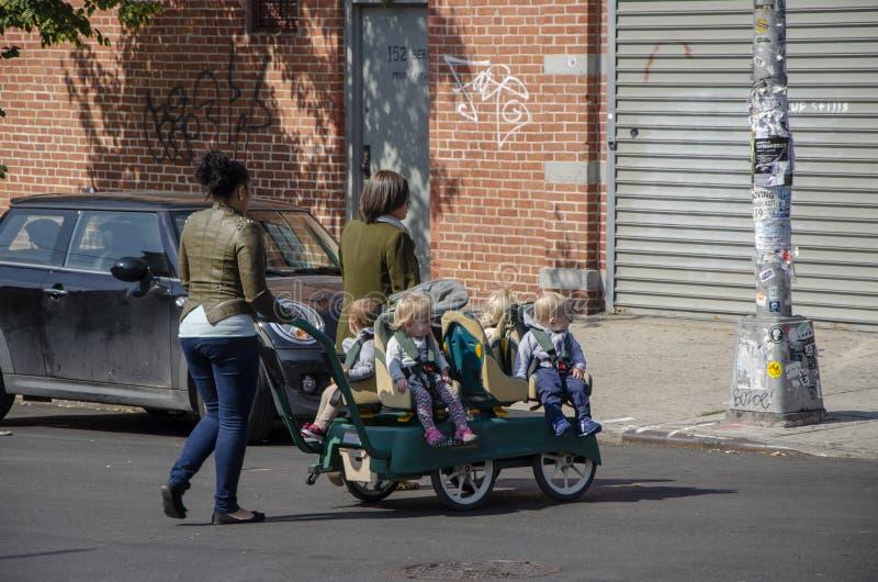 Crianças no carrinho de criança, infantes que dão uma volta através das ruas de Brooklyn New York City fotos de stock