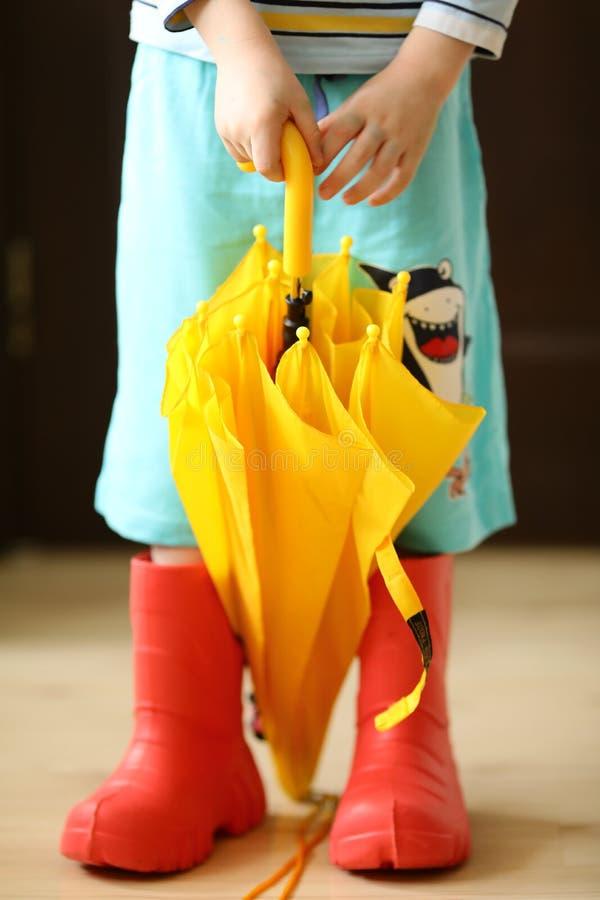 Crianças no desgaste colorido dos rainboots consideravelmente fresco e nos guarda-chuvas fotografia de stock