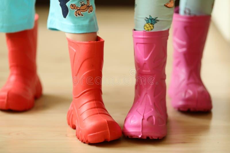 Crianças no desgaste colorido dos rainboots consideravelmente fresco e nos guarda-chuvas foto de stock