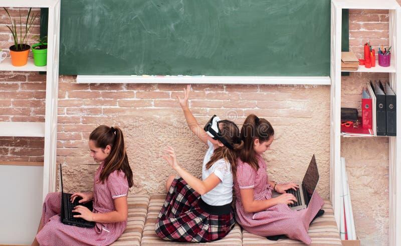 Crianças no espaço da escola com os dispositivos que sentam-se no assoalho Educação, escola moderna, aprendizagem, tecnologia e fotografia de stock