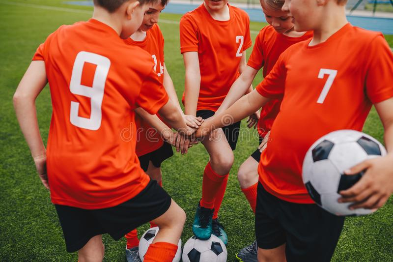 Crianças no futebol Team Putting Hands do futebol dentro Escola Team Huddling do futebol dos meninos imagens de stock